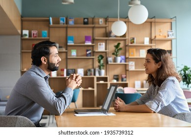 Indian male hr specialist manager, employer, boss listening female latin candidate at job interview, consulting client at office meeting. Hiring and employment, human resources, recruitment concept.