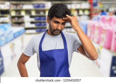 Indian male hypermarket or supermarket worker touching painful forehead with fingers as migraine caused by stress concept