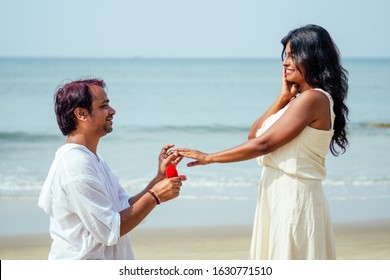 indian male making proposal with engagement ring and roses to his girlfriend at sea beach.Valentine day at Goa