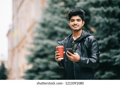 Indian male student texting on smartphone in the street
