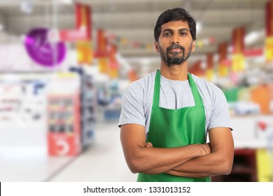 Indian male supermarket or hypermarket employee portrait picture  wearing green apron with crossed arms and serious expression