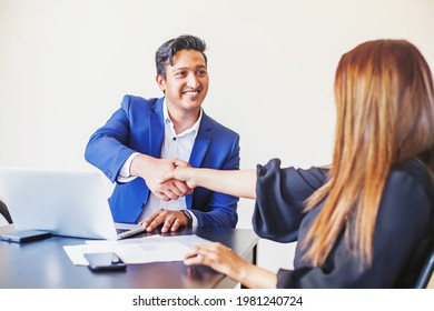 Indian man in business suit shaking hand of an onboarded female customer