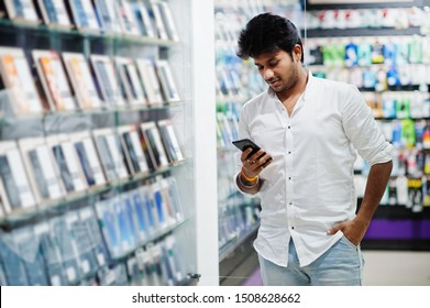 Indian man customer buyer at mobile phone store choose his new smartphone. South asian peoples and technologies concept. Cellphone shop.
