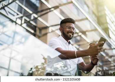 Indian man drinking coffee while standing on the street and use phone
