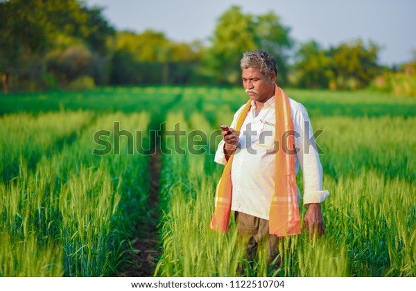 Indian man in a field talking on phone