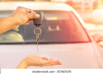 Indian man giving modern car keys ready for rental - Concept of transportation with automobile second hand sale and trade - Warm filtered look with artificial sunlight - Focus on hand keys