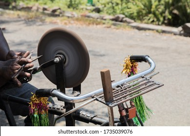 an Indian man holding a steel scissor in his hand to sharpen it on the rotating whetstone which is connected to the rear wheel of his bicycle through a string