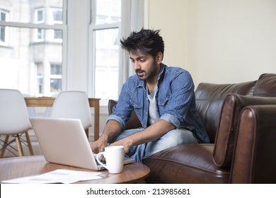 Indian man at home on sofa using a laptop.