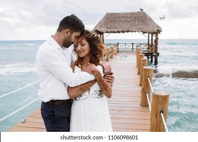 Indian man hugs his woman tender standing on the wooden quay over the sea