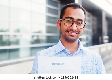 Indian man looking for job and holding his cv, looking at camera