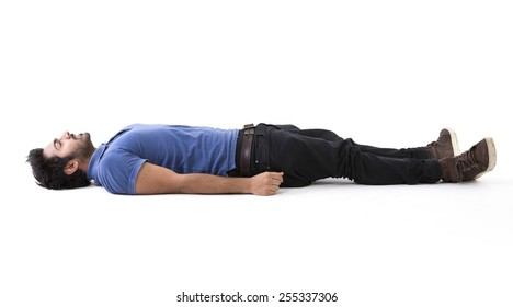 Indian man lying on floor. Full-length image. Isolated on white background.