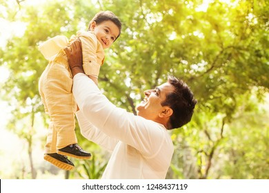 Indian man proudly lifting his son up in the park