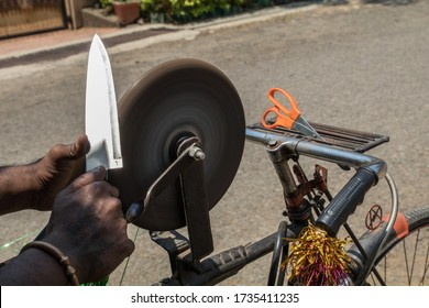 an Indian man sharpening a kitchen knife on the rotating whetstone which is connected to the rear wheel of his bicycle through a string