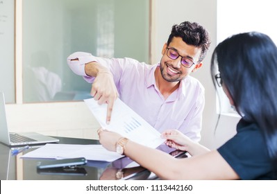 Indian man showing fact sheet with graphs to a woman