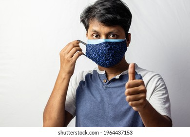 An Indian man shows thumbs up to double masking during covid-19 pandemic, healthcare concept - Shutterstock ID 1964437153