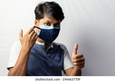 An Indian man shows thumbs up to double masking during covid-19 pandemic, healthcare concept - Shutterstock ID 1964637709