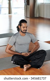 Indian man sitting in lotus position on the floor