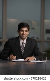 Indian man sitting at table writing