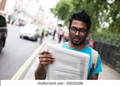 indian man in the street reading a newspaper