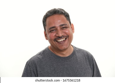 An Indian man in a studio shoot. Smiling to the camera against a white background.