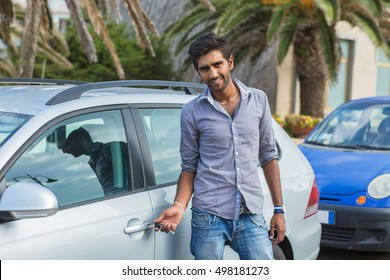 Indian man unlocks car door alarm systems with remote control. Vehicle convenience safety security system