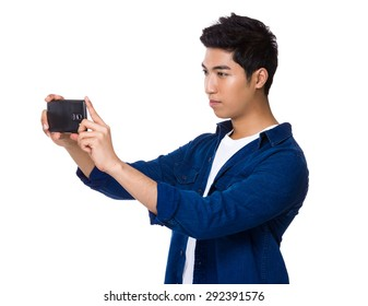 Indian man using cellphone for taking photo