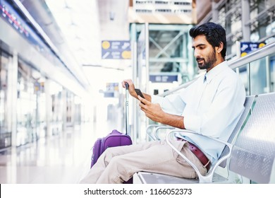 Indian man using his phone in airport terminal