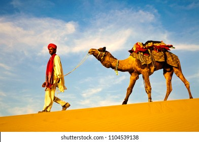 Indian man walking through the desert with his camel