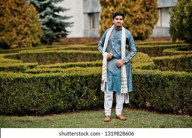 Indian man wear on traditional clothes with white scarf posed outdoor against green bushes at park.