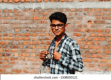 Indian man wearing glasses and stethoscope around his neck staring at the camera
