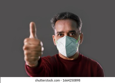 Indian Man wearing a N95 mask and showing thumbs up for protection against virus, dust, pollution and smog