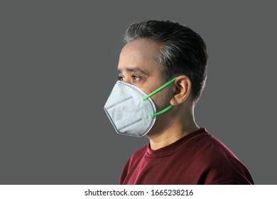 Indischer Mann mit einer N95-Maske zum Schutz gegen Viren, Staub, Verschmutzung und Smog