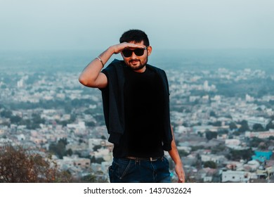 Indian man wearing sunglasses staring at the camera with hands above his eyes