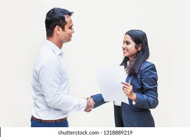 Indian man and woman in office clothes shaking hands