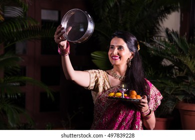 Indian married Woman celebrating Karva Chauth festival at night