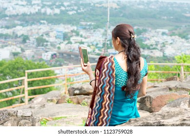 Indian Married Woman taking selfie with smart phone on top of the hill