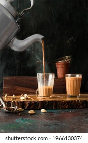 indian masala chai or tea ion ttraditional glasses, with kettle, spices and tea leaves.