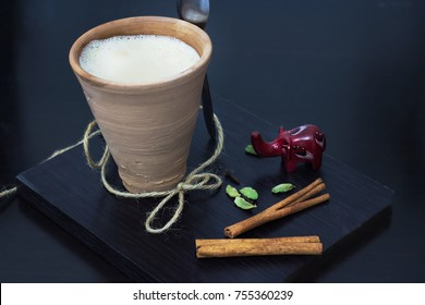 Indian masala chai tea karak with spices and milk, in clay glass. Black wooden background. Selective focus