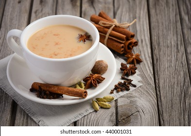 Indian masala chai tea, spiced tea with milk on rustic wooden table, selective focus, copy space