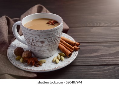 Indian masala chai tea. Spiced tea with milk on dark wooden table. Selective focus, horizontal with copy space.