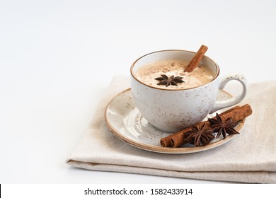 Indian Masala chai tea. Traditional Indian hot drink with milk and spices on white background close up.