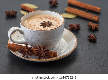 Indian Masala chai tea. Traditional Indian hot drink with milk and spices on dark stone background close up.