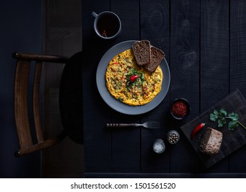 Indian masala omelet with chili pepper and coriander on dark wooden background