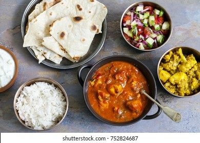 Indian meal with chicken tikka masala, aloo gobi, raita, flatbreads and salad