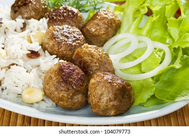 Indian meal of lamb koftas or meatballs, with pilau rice and salad. Basmati rice is cooked with raisins and almonds.