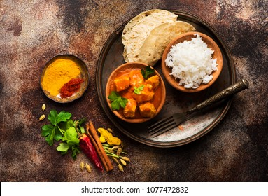 Indian meat dish with rice and naan bread. Chicken tikka masala spicy.