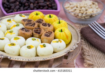 Indian Mix Sweet Food Apple Shaped Peda With White Peda or Bhakarwadi Also Know as bakarwadi, bakarvadi, pedha or peday is a prepared in thick, semi-soft pieces. the main ingredients are khoya, sugar