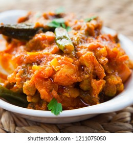 Indian Mixed Vegetable Curry - -  Asian cuisine vegetarian or vegan popular dish -  tomato, potato, okra, cauliflower, sweet potato, butternut squash, green peas and chilli peppers.