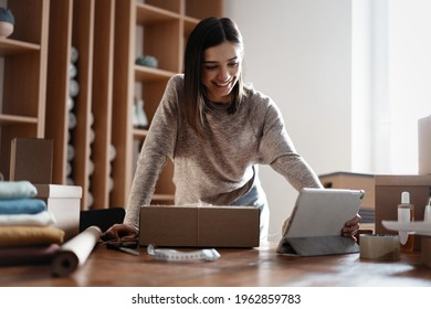 Indian mixed-race female seller using tablet checking ecommerce clothing store orders