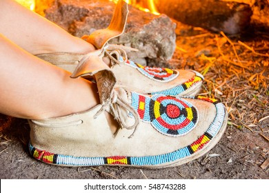 Indian moccasins embroidered with beads near the bonfire.